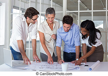 Attractive business people working hard on plans -...
