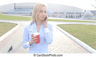 Attractive business woman commuter talking on the phone walking in city