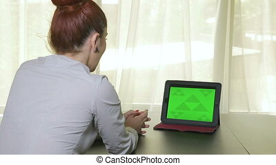 Attractive business woman having a video conference from the tablet pc