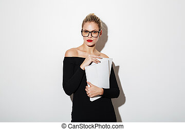 Attractive business woman in dress and eyeglasses holding documents
