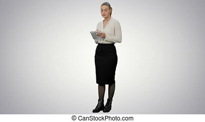 Attractive business woman makes some calculations and writes them down on paper on white background.