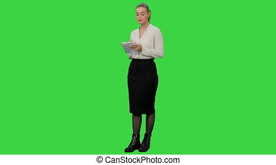 Attractive business woman makes some calculations and writes them down on paper on a Green Screen, Chroma Key.