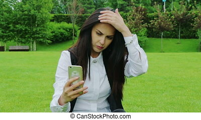 Attractive business woman sitting in the park and fixing her hair