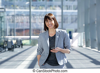 Attractive business woman smiling with mobile phone