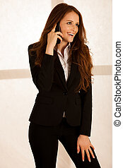 attractive business woman talk on a smart phone in her office gesture success