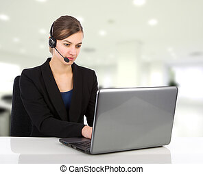 Attractive business woman with headset working on a laptop