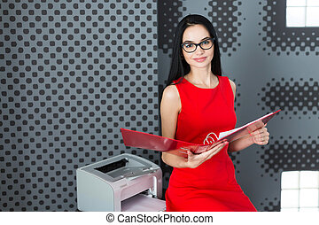 Attractive businesslady in red dress and glasses stand near the