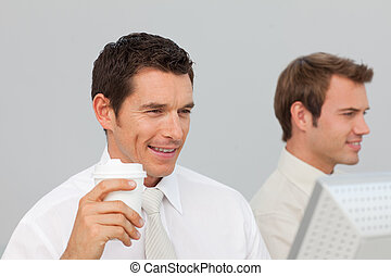 Attractive businessman drinking coffee in the office while he is using the computer