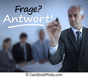 Attractive businessman holding a marker and writing frage antwort in front of business people
