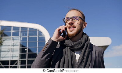 Attractive businessman in a beautiful jacket with scarf talking on the phone, he walking near the office building, laughing and looking very happy