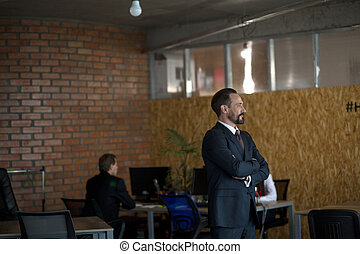 Attractive businessman in back suit is standing in profile in his office with crossed arms. Two colleagues are working behind.