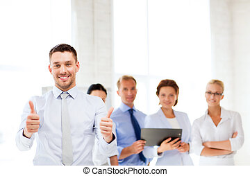 businessman in office showign thumbs up