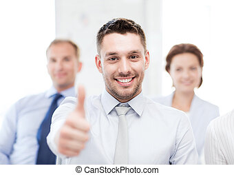 businessman in office showign thumbs up - attractive...