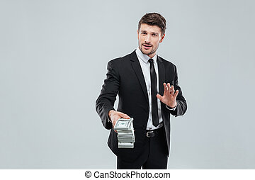 Attractive businessman in suit and tie giving you money back