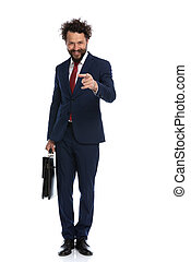 businessman pointing at the camera and holding a briefcase