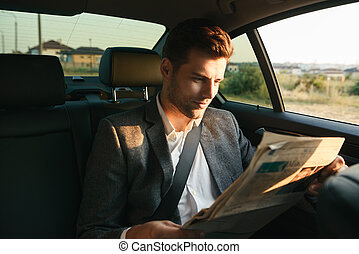 Attractive businessman reading newspaper