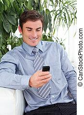 Attractive businessman sending a text
