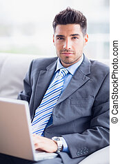 Attractive businessman sitting on couch using his laptop