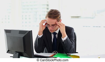 Attractive businessman suffering from headache sitting at...
