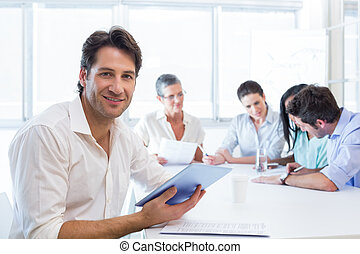 Attractive businessman using a tablet at work