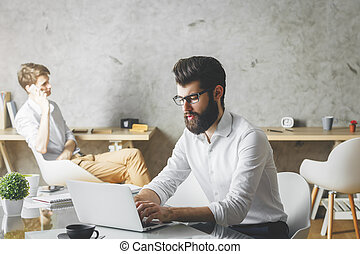 Attractive businessman using laptop