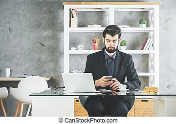 Attractive businessman using smartphone