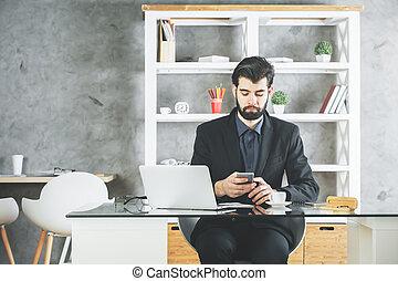Attractive businessman using smartphone