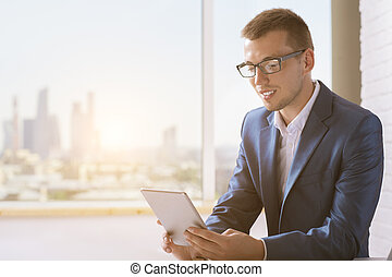 Attractive businessman using tablet