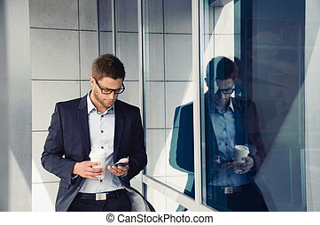 attractive businessman with phone device and coffee in hands on