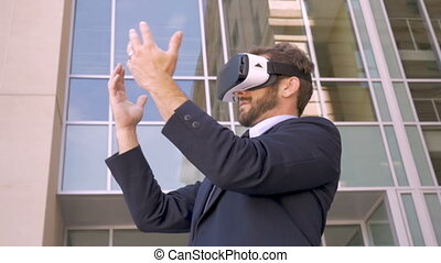 Attractive businessman with VR headset experiencing virtual...