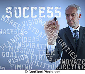 Attractive businessman writing success terms with a marker