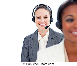Attractive businesswoman and her colleague with headset in a call center