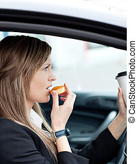 Attractive businesswoman eating and holding a drinking cup while driving to work
