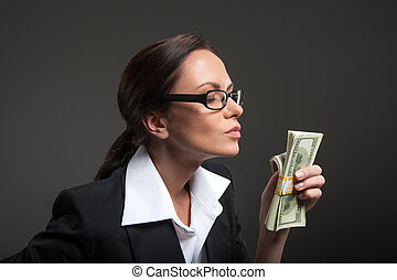 Attractive businesswoman enjoys smell of money on black...