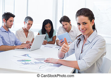Attractive businesswoman giving thumbs up to the camera in the workplace with her fellow coworker friends in the background
