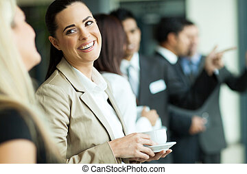 attractive businesswoman having fun conversation with colleague during break