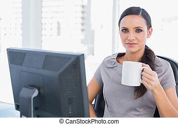 Attractive businesswoman holding mug