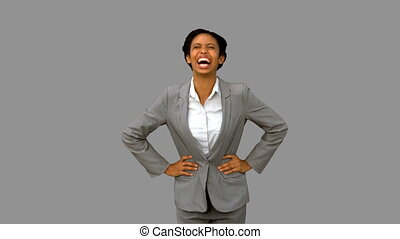 Attractive businesswoman laughing on grey screen in slow...