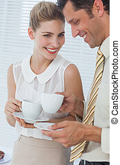 Attractive businesswoman laughing with her colleague while ...