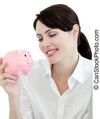 Attractive businesswoman looking at a piggybank