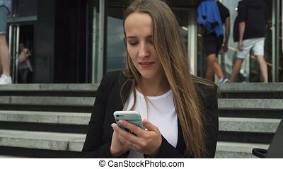 Attractive businesswoman looking at smartphone screen near city building