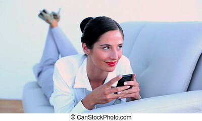 Attractive businesswoman lying on couch