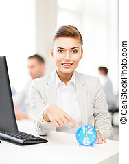 businesswoman pointing at clock in office