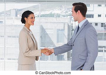 Attractive businesswoman shaking hands to handsome businessman