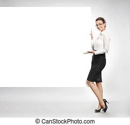 Attractive businesswoman showing empty white board