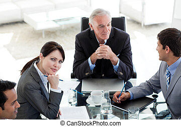 Attractive businesswoman sitting at a conference table with her team looking at the camera
