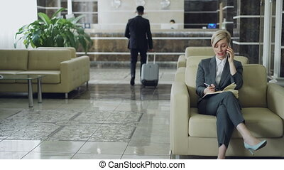 Attractive businesswoman sitting in armchair talking mobile...