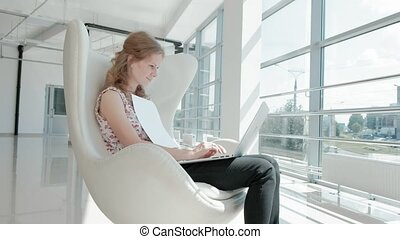 attractive businesswoman sitting on white chair in glass office and working behind laptop