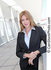 Attractive businesswoman standing outside a building