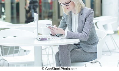 Attractive businesswoman surrounded by devices.